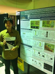Photograph of Youhei Kotsuchibashi next to his winning poster