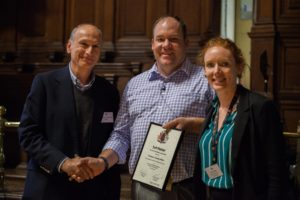 Tim White receiving his award from Dimitris Vlassopoulos and Laura Fisher